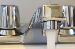 Running Faucet. Bathroom faucet running and wasting water Royalty Free Stock Image