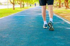 Running feet male in runner jogging exercise with old shoes for health lose weight concept on track rubber cover blue public park. Copy space add text stock image