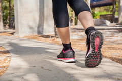 Running feet of young woman going by concrete trail in the park Royalty Free Stock Images