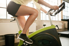 Running at the fitness club. Side view of female in action exercising in health club. Fit young woman running on treadmill in the gym Stock Photos