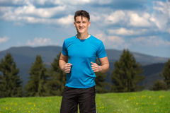 Running fitness man sprinting outdoors in beautiful landscape. Fit male runner training for marathon. Caucasian sport model Stock Photography