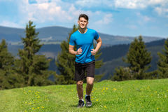 Running fitness man sprinting outdoors in beautiful landscape. Fit male runner training for marathon. Caucasian sport model Royalty Free Stock Photo