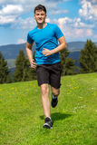 Running fitness man sprinting outdoors in beautiful landscape. Fit male runner training for marathon. Caucasian sport model Stock Image