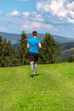 Running fitness man sprinting outdoors in beautiful landscape. Fit male runner training for marathon. Caucasian sport model Royalty Free Stock Photos