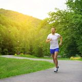 Running fitness man. Sprinting outdoors in beautiful park royalty free stock image