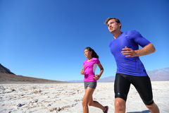 Running fitness sport runners in extreme run. Training in the desert. Athlete running multiracial running couple. Fit caucasian men sports model and sporty stock images