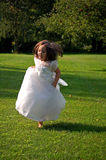 Running Flower Girl. Four year old flower girl running in the grass Royalty Free Stock Images