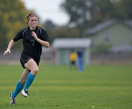 running fotboll för flickaspelare Royaltyfri Bild