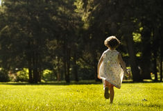 Running Free. Little girl in dress running in backlit field Royalty Free Stock Photo