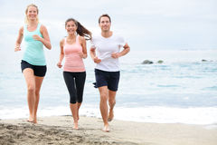 Running friends on beach jogging. Group training. Exercising runners training outdoors living healthy active lifestyle. Multiracial fitness runner people Royalty Free Stock Photos