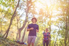 Running is fun- Couple jogging and running outdoors in nature royalty free stock photos