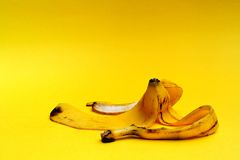 Running Gag. Banana skin on yellow background royalty free stock photo