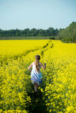 Running girl. An image of a girl running in the yellow field stock image