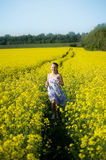 Running girl. An image of a girl running in the yellow field royalty free stock photos