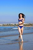 Running girl. A girl in the bikini running on the seabank stock image