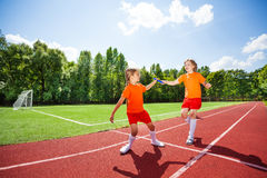 Running girl with baton hands it to other runner Stock Photography