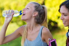 Running girl drinking water after running. Royalty Free Stock Photography