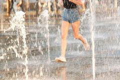 Running girl in fountain sprays. Girl in shorts running in a city summer park between jets and spray of a fountain stock photos