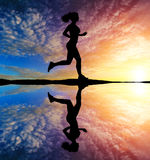 Running girl at sunset silhouette Royalty Free Stock Photo