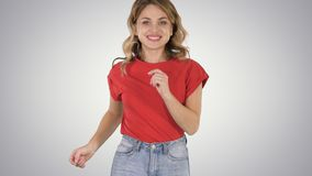 Running girl wearing red t-shirt and jeans Smiling on gradient background. royalty free stock image