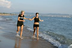 Running girls on a beach Stock Images