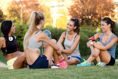Running girls having fun in the park with mobile phone. Stock Image