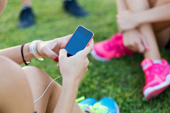 Running girls having fun in the park with mobile phone. Royalty Free Stock Photography