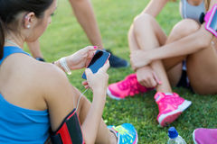 Running girls having fun in the park with mobile phone. Royalty Free Stock Image