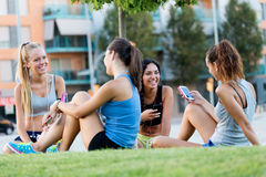 Running girls having fun in the park with mobile phone. Royalty Free Stock Images