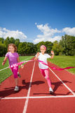 Running girls try reaching the ribbon excited Royalty Free Stock Photography