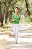 Running in green forest. Young woman jogging in green forest, smiling and looking in camera Stock Photo