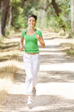 Running in green forest. Young woman jogging in green forest, smiling and looking in camera Stock Images