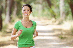 Running in green forest. Young woman jogging in green forest, smiling and looking in camera Stock Photos