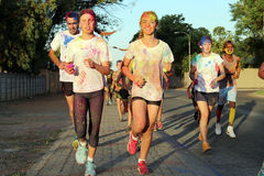 Running group of teens and man covered with powder paint. Rustenburg Marathon Club Rainbow Run - NOVEMBER 25: Running group of teens and man covered with powder Stock Photo