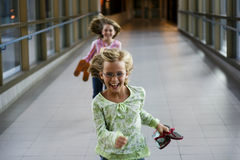 Running in the hall. Two girls running in the hall with smiles on their faces Royalty Free Stock Photo