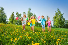 Running happy children with balloons in summer. Running happy children with balloons in green field in summer Stock Images