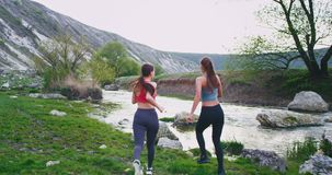 Running hard two sports women in the middle of wonderful landscape view they stopped for a bit to take a break and stock footage