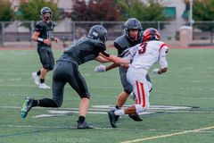 Running High School Football Players. High school football players chase after each other during a game royalty free stock photos