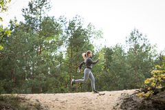 Running on hillock. Active young girl running on sandy hillock stock photo