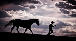 Running Horse & Cowboy Silhouette. Silhouette of a cowboy being chased by his horse under a cloudy sunset sky Royalty Free Stock Photo