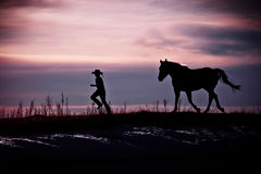 Running Horse & Cowboy Silhouette. Silhouette of a cowboy being chased by his horse under a cloudy sunset sky Stock Photo