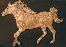 Running Horse . Gold colored symbol of the horse stock image
