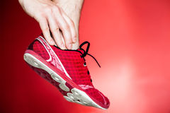 Running injury, leg and ankle pain. Physical running injury and leg ankle pain, sport shoes and hand massage over red background Stock Photo