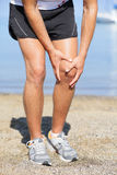 Running injury - Man out jogging with knee pain. Closed up veiw of the hands of a man out jogging on the beach clutching his knee as though in pain Stock Photo