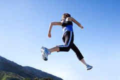 Running & Jogging. A low-angle view of a woman taking a morning run. Different perspective of her taking a leap along her jogging path stock photography