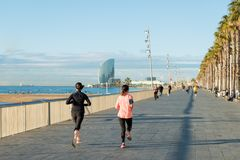 Running jogging on Barcelona Beach, Barceloneta. Healthy lifestyle people runners training outside on boardwalk. Multiracial coup royalty free stock photo