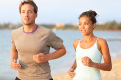Running jogging couple training on summer beach. Running young pretty couple jogging on summer beach sand in sun. Exercising Caucasian fitness model and Stock Images