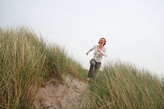 Running for Joy. A young Caucasian woman running for joy among sand dunes with a big smile on her face Royalty Free Stock Photo