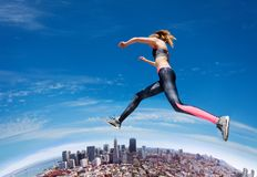 Jumping fit girl across blue sky stock photo