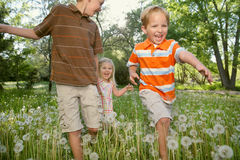 Running Kids. Three sibling children running up close and holding hands in nature Royalty Free Stock Photos